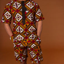 African print shorts with drawstring waist hand-made from red, yellow, white and black ankara wax print in a geometric pattern