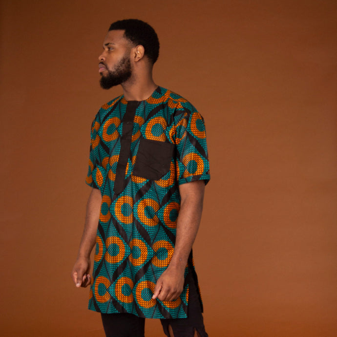 African print kaftan top made from green and orange ankara wax print fabric in a geometic pattern featuring black trim in the pockets and neckline