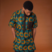 Load image into Gallery viewer, African print kaftan top made from green and orange ankara wax print fabric in a geometic pattern featuring black trim in the pockets and neckline