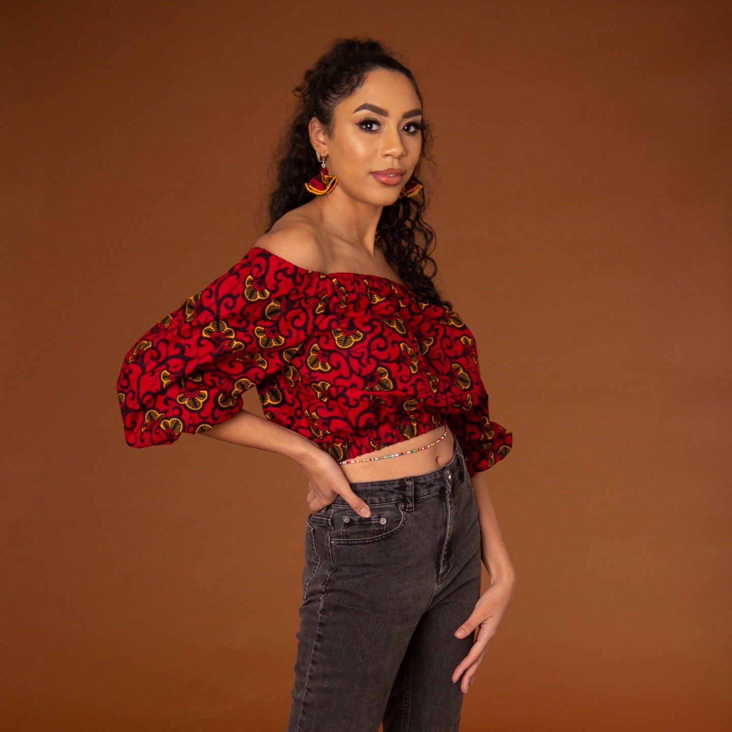 Off-shoulder African print crop top with three-quarter balloon sleeves and elasticated waist, arms and neckline in red and yellow ankara wax print