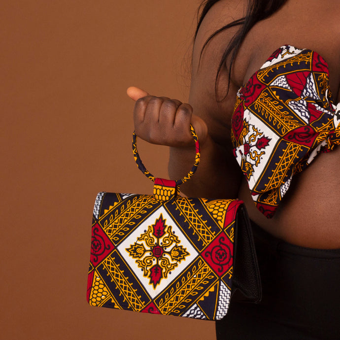 Black leather, velvet lined clutch bag overlaid with red, yellow, white and black ankara wax print in a geometric pattern with a ring handle
