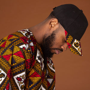 African print snapback cap in a striking red, yellow, white and black ankara wax print geometric pattern