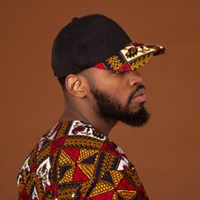 Load image into Gallery viewer, African print snapback cap in a striking red, yellow, white and black ankara wax print geometric pattern