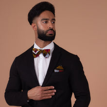 Load image into Gallery viewer, Man wearing Red, white, navy blue and yellow pocket square and bow tie with a black blazer and a white shirt looking to the left