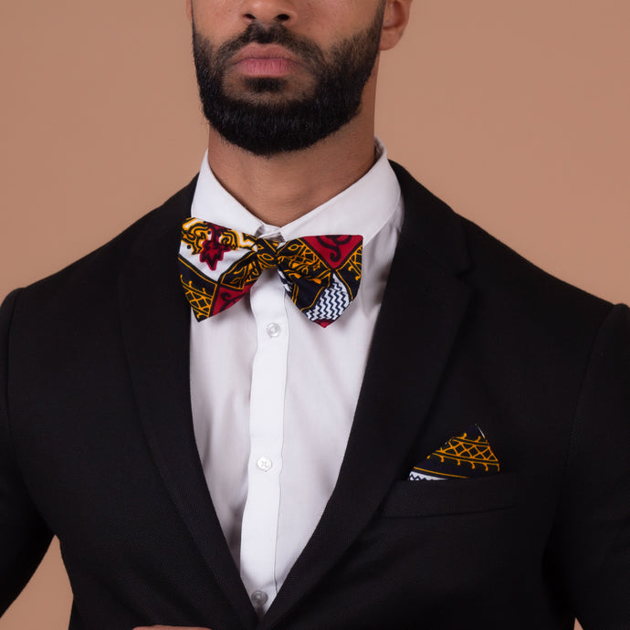 Man wearing Red, white, navy blue and yellow pocket square and bow tie with a black blazer and a white shirt