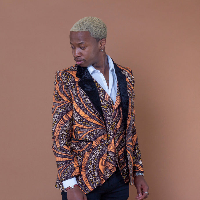 Men's blazer made from brown and orange african print ankara wax fabric finished with velvet lapels on the neckline and worn with matching waistcoat and white shirt