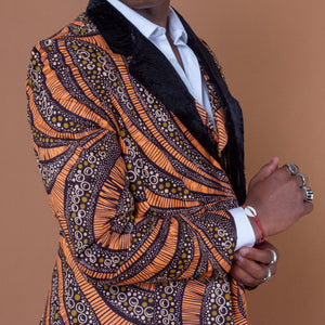 Men's blazer made from brown and orange african print ankara wax fabric finished with velvet lapels on the neckline