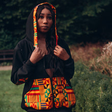 Load image into Gallery viewer, Black woman in a black hoodie with a multicoloured kente pattern on the pocket and hood he hood is on top of her long black hair and she is looking straight ahead