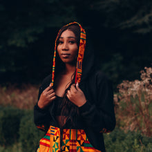 Load image into Gallery viewer, Black woman in a black hoodie with a multicoloured kente pattern on the pocket and hood he hood is on top of her long black hair and she is looking to the side