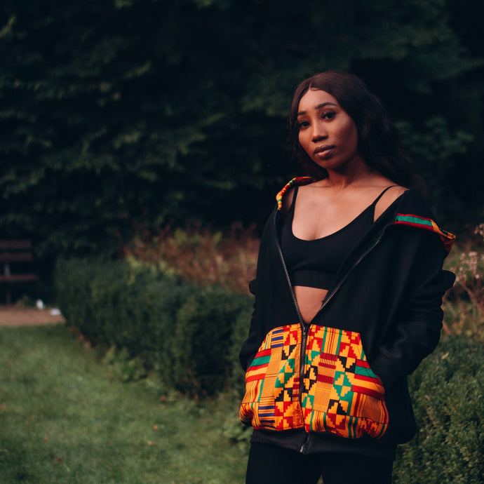 Black woman in a black hoodie with a multicoloured kente pattern on the pocket and hood he hood is on top of her long black hair and she is looking sideways