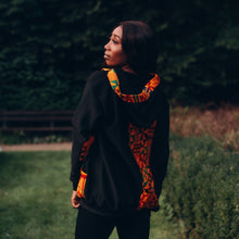 Load image into Gallery viewer, Black woman in a black hoodie with a multicoloured kente pattern on the pocket and hood he hood is on top of her long black hair and she is looking sideways with kente on her back and hood facing us