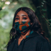 Load image into Gallery viewer, Black girl in a green and orange face mask against a leafy background