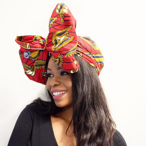 Red african print head wrap made from red, yellow, black and white ankara wax print ties as an oversized bow
