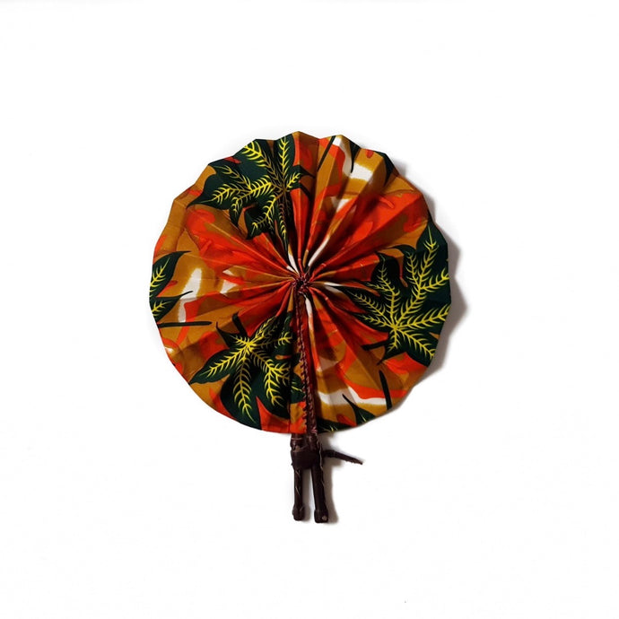 African print fan made from ankara wax print in an orange, yellow and black autumnal leaf pattern finished with dark brown leather clasp