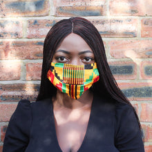 Load image into Gallery viewer, Black girl with braided hair in an African print Kente cotton face mask with a red, green, black and yellow pattern against a brown and black brick wall