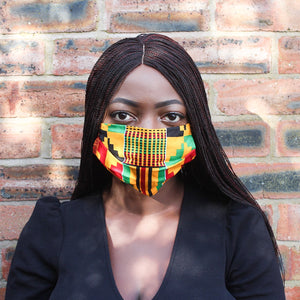 Black girl with braided hair in an African print Kente cotton face mask with a red, green, black and yellow pattern against a brown and black brick wall