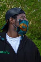 Load image into Gallery viewer, Side angle of man wearing a geometric African print face mask in a green and orange ankara wax print against a lush green foliage background