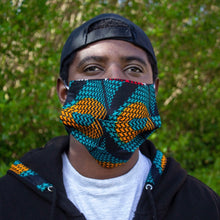 Load image into Gallery viewer, Man wearing a geometric African print face mask in a green and orange ankara wax print against a lush green foliage background
