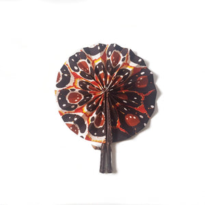 Expanded orange, brown and white African wax print fan finished with dark brown leather fastener
