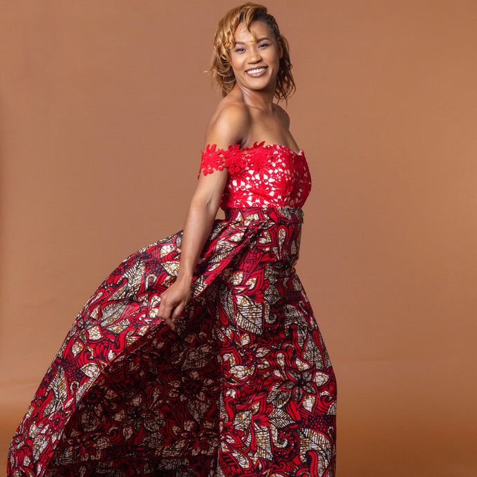 Figure hugging floor-length Ankara wax print pencil dress in floral pattern featuring a lace bodice with a sweetheart neckline and off-shoulder straps. This dress can be coupled with a matching cape belt.