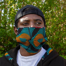 Load image into Gallery viewer, Black Man wearing a geometric African print face mask in a green and orange ankara wax print and snapback cap against a lush green foliage background