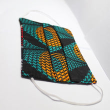 Load image into Gallery viewer, Black and orange african print face mask with elastic straps against a white background