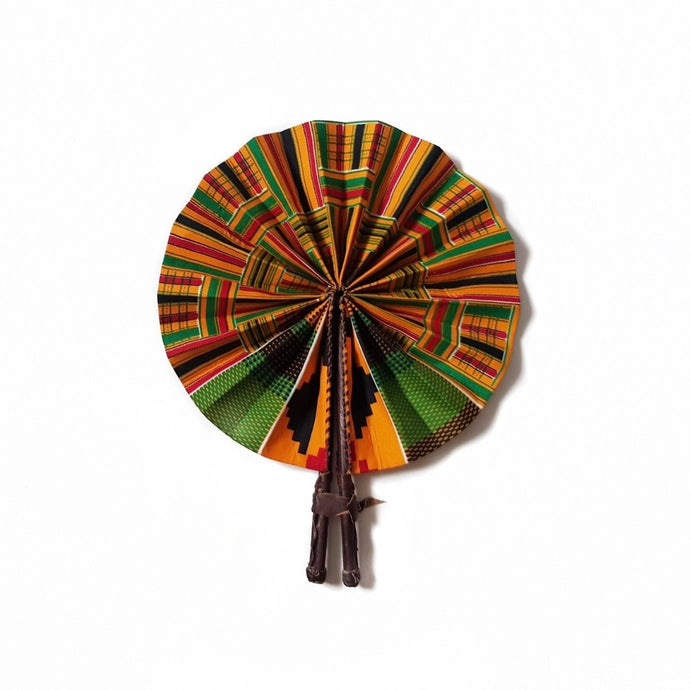 Multicoloured African print fan made from green, yellow, red and black kente wax print and finished with a dark brown leather clasp