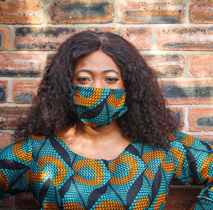 Black woman with Afro curly hair wearing African Print Ankara green, orange and black face mask and matching top pictured against a brick wall