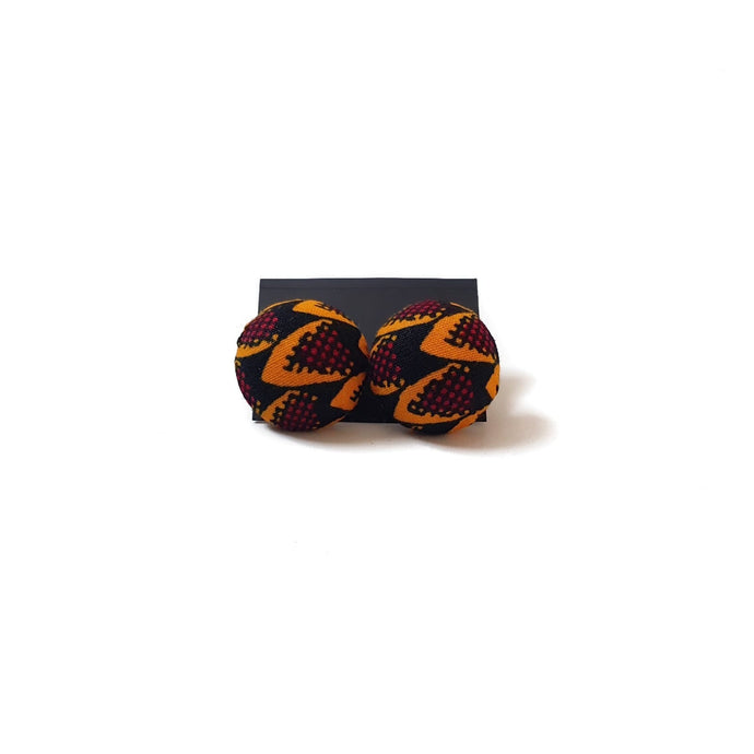 Button stud earrings in light orange, black and dark mahogany pattern on a black card and white background