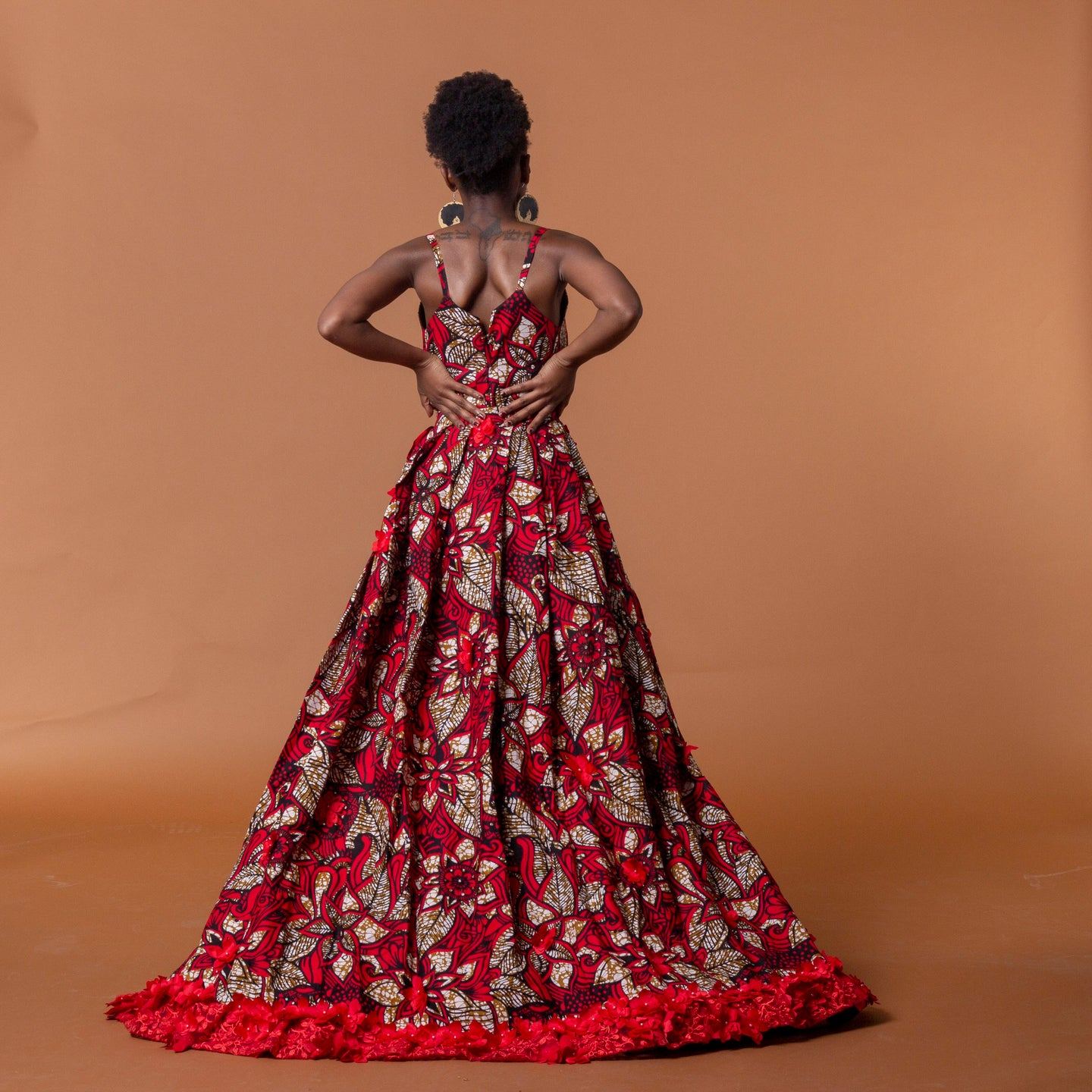 Back view of red african print cape in floral ankara wax print fastened at the waist