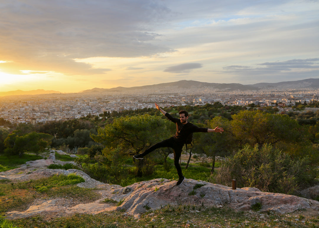 Man balancing on top of a hill in athens, greece