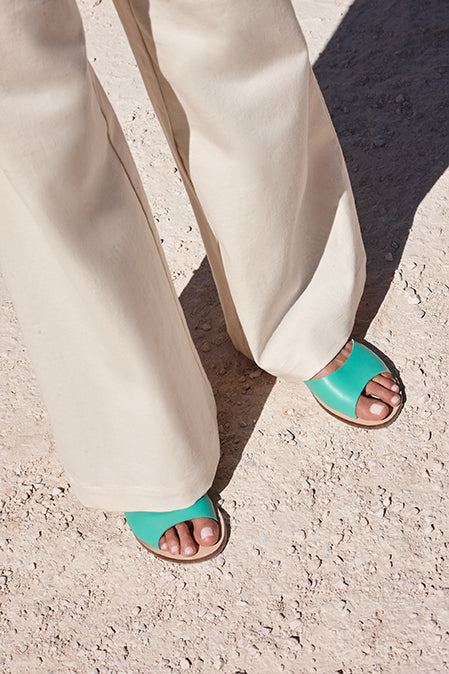 Shot of white trousers with mint leather summer sandals, handmade in Greece