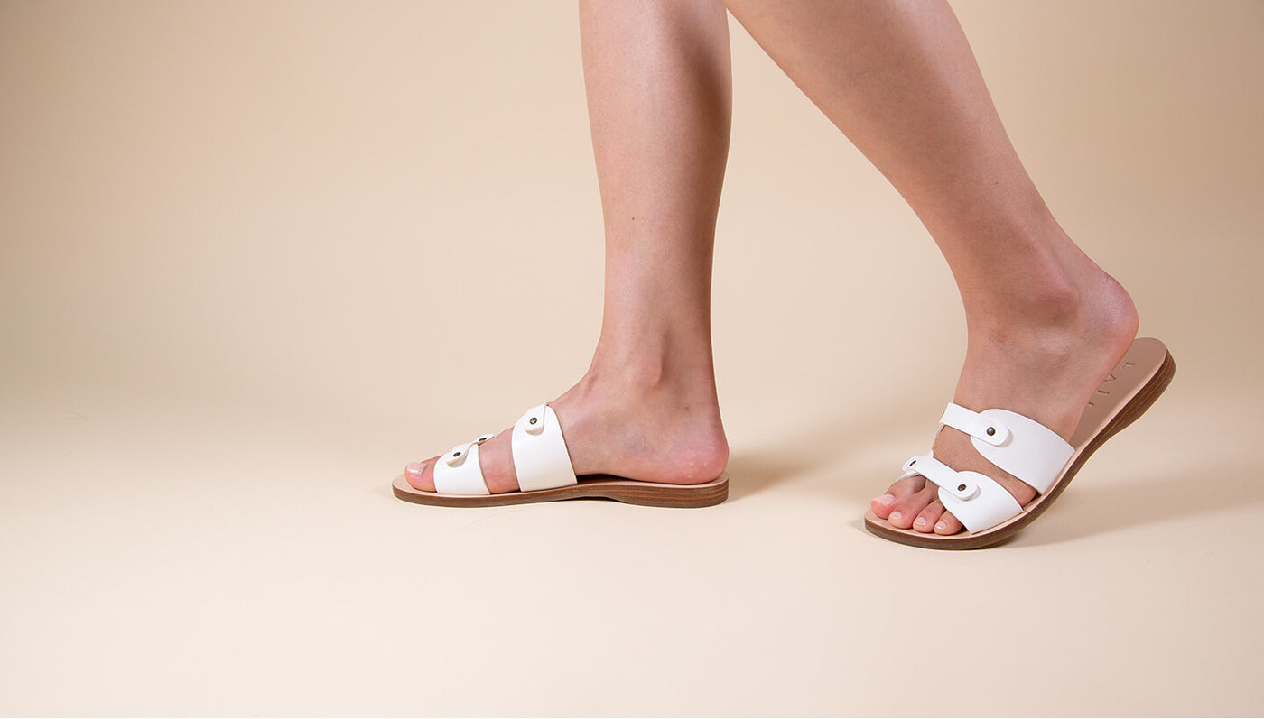 Model wearing Greek white leather sandal slides