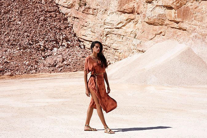 athina wearing golden gladiator flat sandals walking in a stone quarry, wearing a red dress