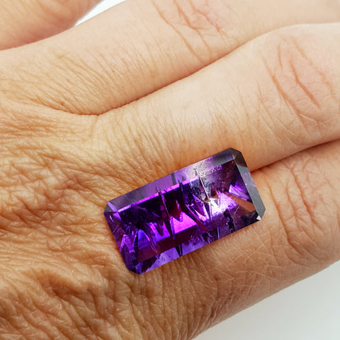 A large, rectangle-shaped Arizona amethyst sits on top of a hand. The gem has color zones of both white and purple, and is laser etched with the outline of the Four Peaks.