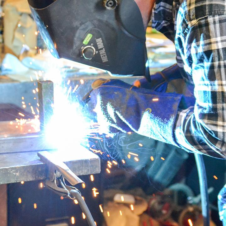 welder using torch with heat resistant gloves