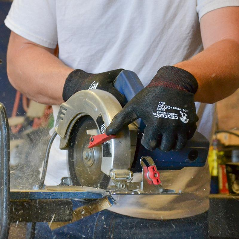 man wearing woodworking carpentry gloves using a table saw