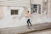A woman runs in the goodbody goodmommy leggings.