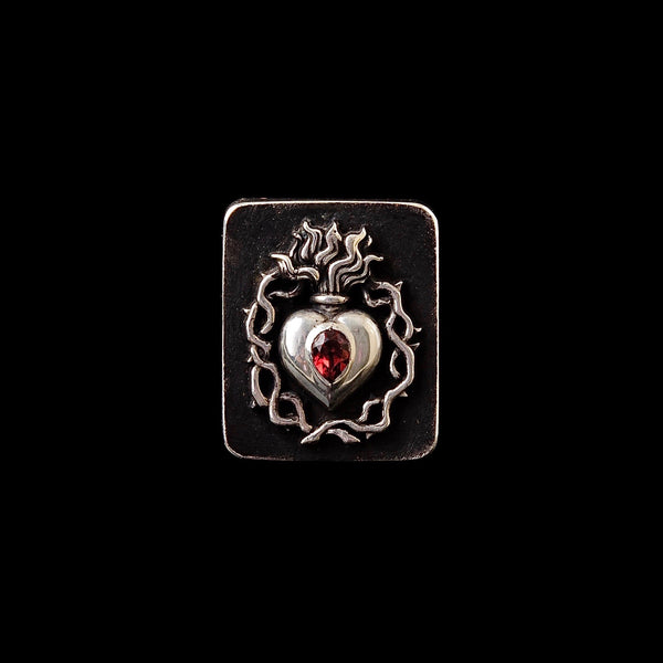 Sacred Heart Ring with a red garnet on a black background