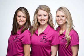 Group photo of three sisters wearing pink polo shirts