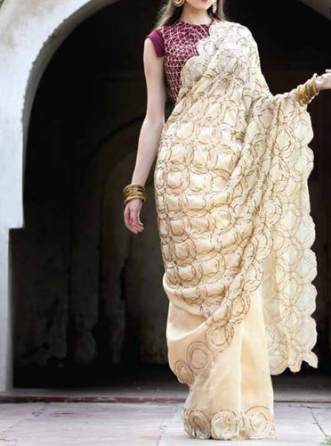 Beige embroidered saree with embroidered blouse.
