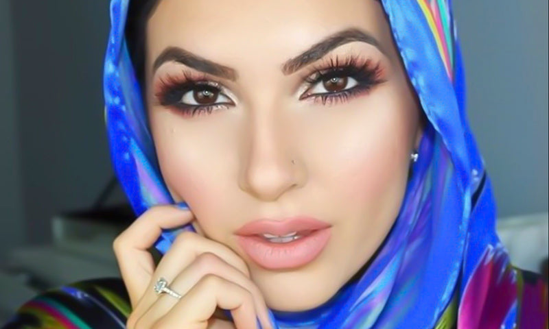 young woman in blue scarf wearing glam makeup