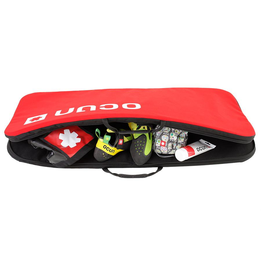 Ocun Paddy SitCase crash pad, in red, shown open and in use as a storage bag