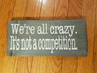 We're all crazy it's not a competition hand-painted wood sign