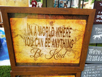 In a World Where You Can Be Anything Be Kind sign with antique brown and gold world map