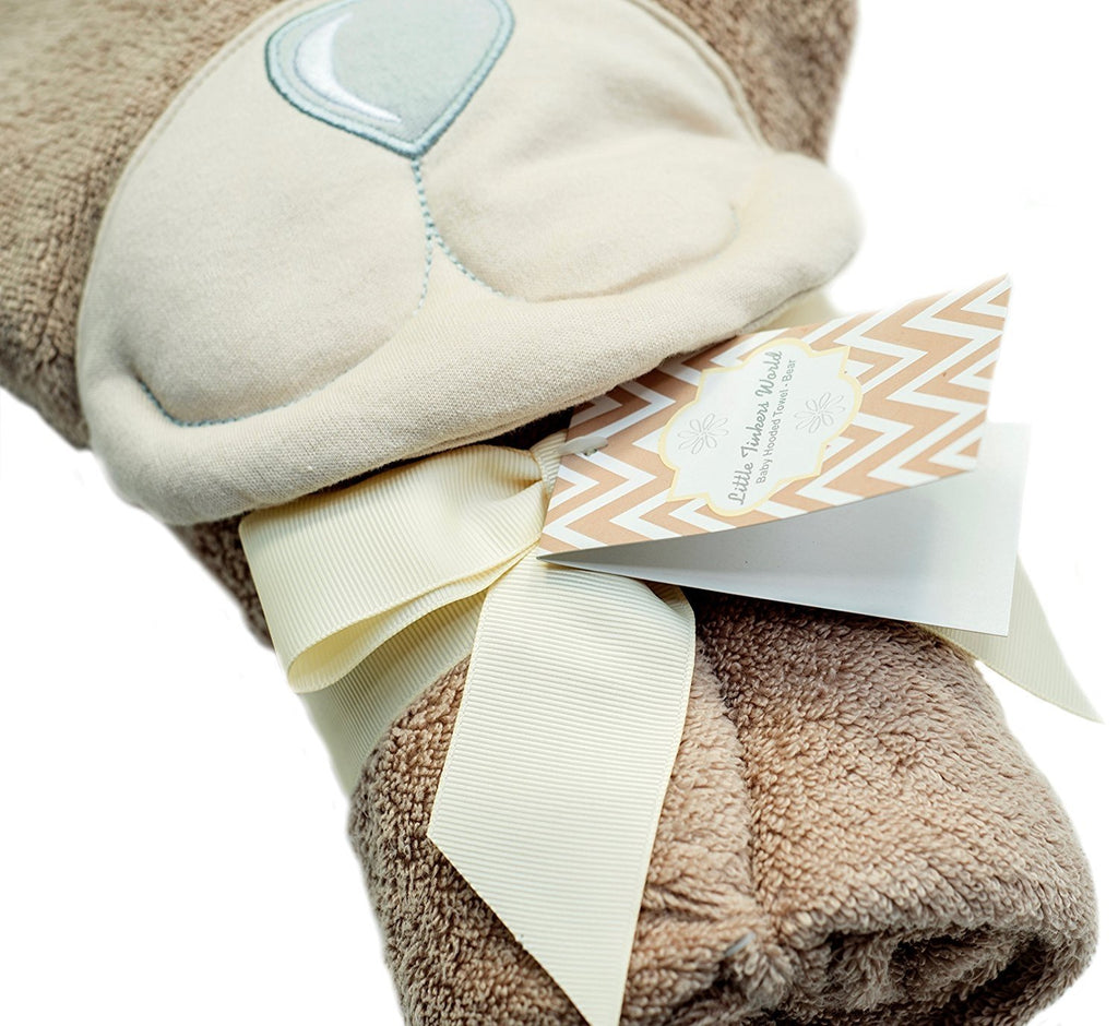ALT = Bear Baby hooded towel folded with a beige ribbon around it shot from a side angle