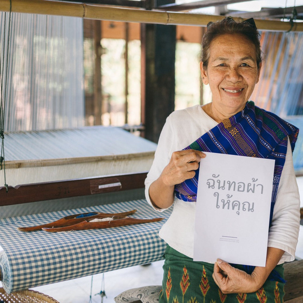"""An artisan stands by her recently created handloom fabric holding a """"I made your fabric' sign in Thai language."""