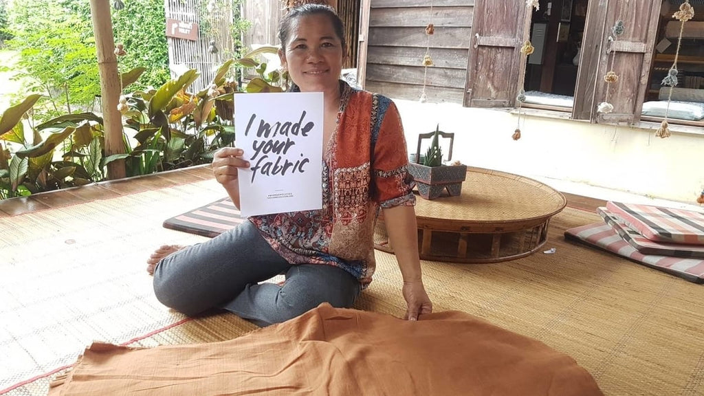 """Thai woman artisan proudly sitting with the sustainable cotton fabric she has handwoven. The woman artisan is holding a sign that reads """"I made your fabric"""""""