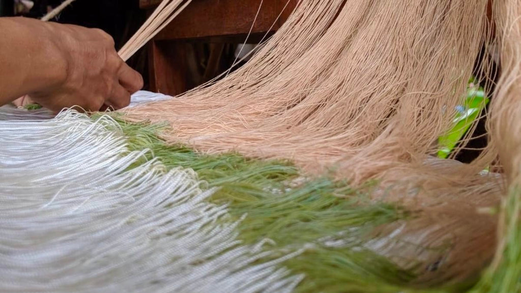 Image shows hands tying the sustainable cotton yard thread on to the previously woven yard ready for weaving the Handmade Cherrada Dress - Rare & Fair