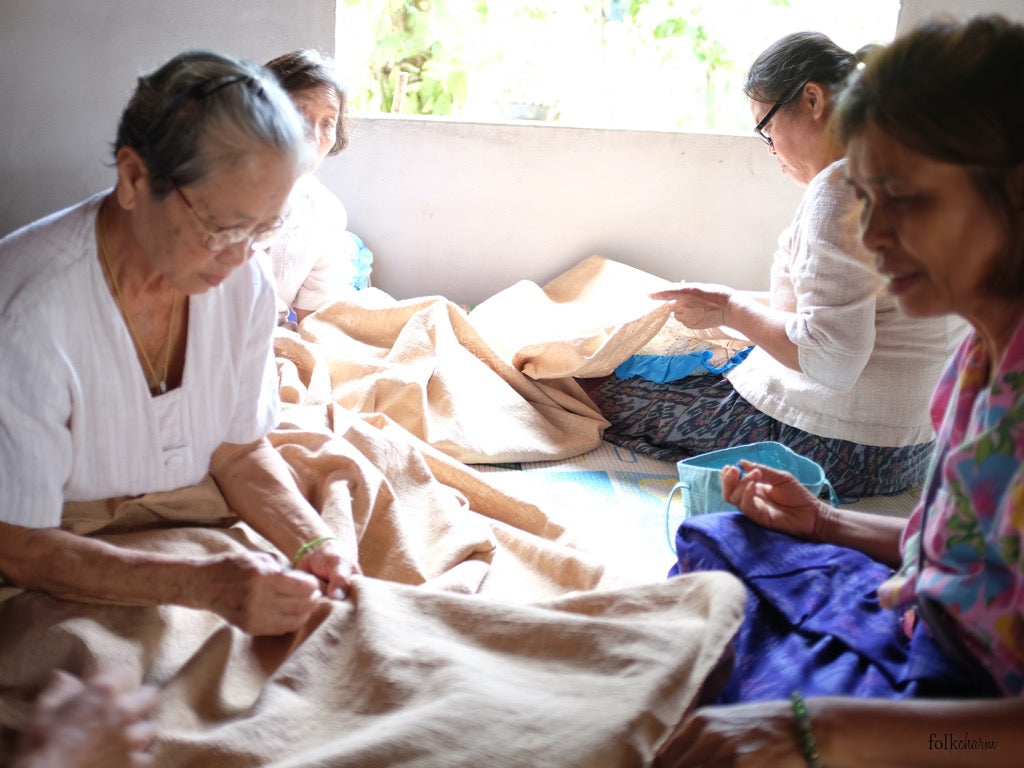 Members of FolkCharm Crafts inspecting the organic cotton after weaving.